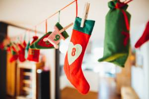 Red and green miniature stockings hung by clothespins into garland
