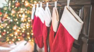 Red and white stockings hung on hooks by a Christmas tree