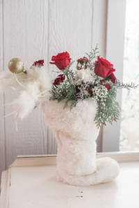 Roses, baby's breath, and greenery overflowing out of a white fur stocking